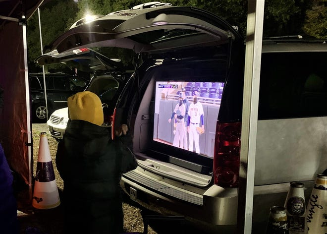 "A young ECU fan watches Friday night's opener on a TV run by a generator with members of the ""Left Field Megaphone Crew""  in a parking lot across the street from Clark-LeClair Stadium. (Photo: Joey Chandler, StarNews)"