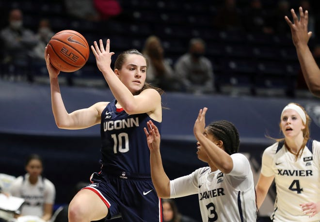 Connecticut guard Nika Muhl (10) looks to pass over Xavier guard Aaliyah Dunham (3) during the first half of an NCAA college basketball game Saturday, Feb. 20, 2021, in Cincinnati.