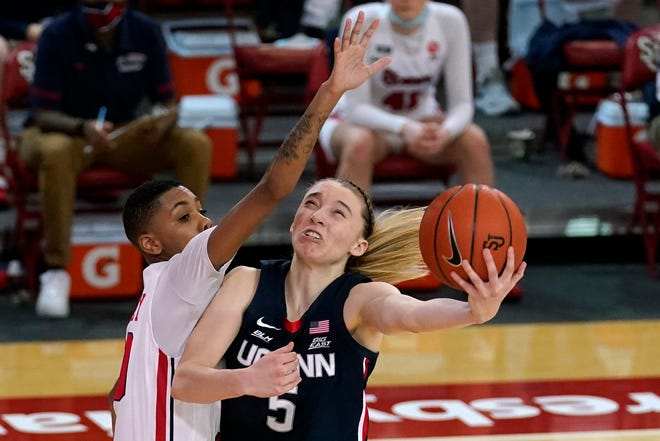 St. John's guard Kadaja Bailey (30) fouls Connecticut guard Paige Bueckers (5) during the Huskies' win in New York.