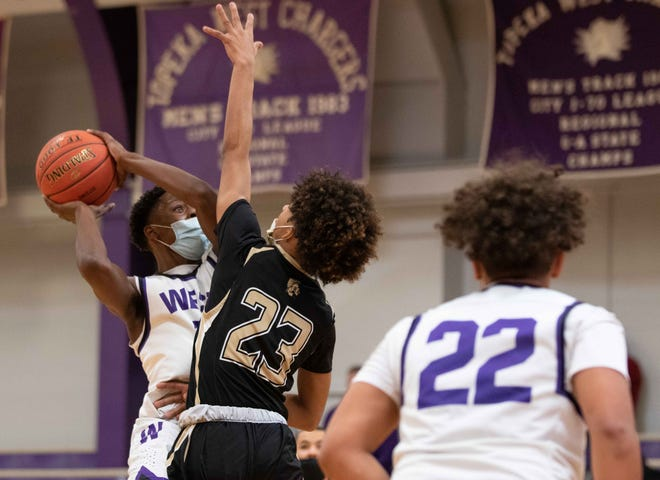 Topeka West senior Marque Wilkerson takes a guarded shot against Topeka High's Mister Cameron during Saturday's 68-40 win that clinched the outright Centennial League title for the Chargers.