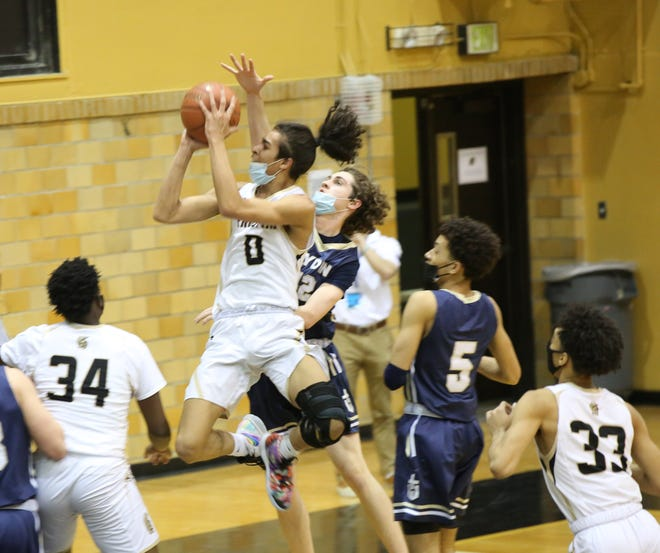 Topeka High's Isiah Esquibel goes in for a layup during Friday's game against Hayden. Esquibel scored 14 points on senior night to help the Trojans to a 45-38 win.