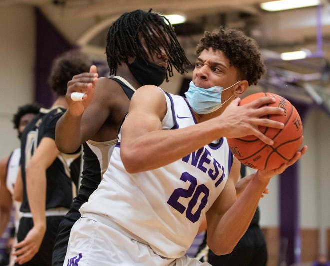 Topeka West senior Trevion Alexander spins past Topeka High's Jalen Smith during Saturday's game at Topeka West. Alexander scored 16 to lead the Chargers to a 68-40 win that clinched the outright Centennial League title.