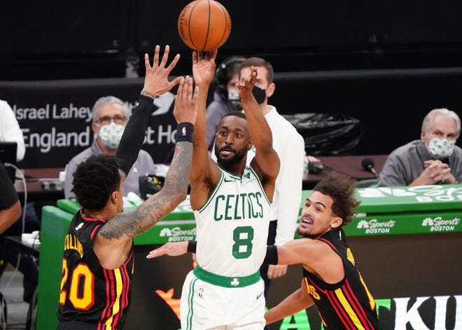 The Celtics' Kemba Walker shoots against Hawks forward John Collins, left, and guard Trae Young in the second quarter Friday night at TD Garden.