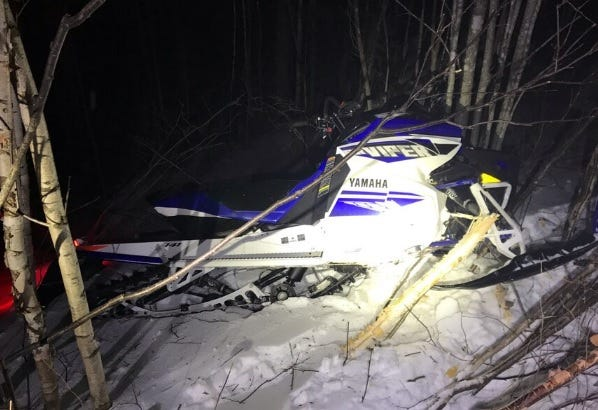 A damaged snowmobile at the scene of a crash in Maine that killed a Spencer man Friday night.