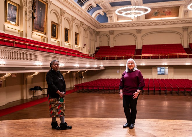 Public art call administrator and preservationist Gloria D. Hall, left, and executive director Kathleen Gagne look toward the balconies at Mechanic's Hall where at two new portraits of Black Americans will join the gallery of portraits in the Great Hall.