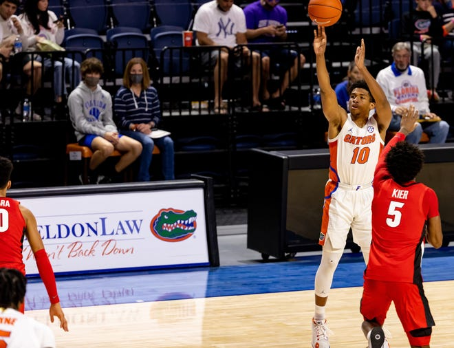 Florida guard Noah Locke attempts a three-point shot Saturday against Georgia at Exactech Arena. Locke surpassed the milestone of making more than 200 3-pointers for his career.