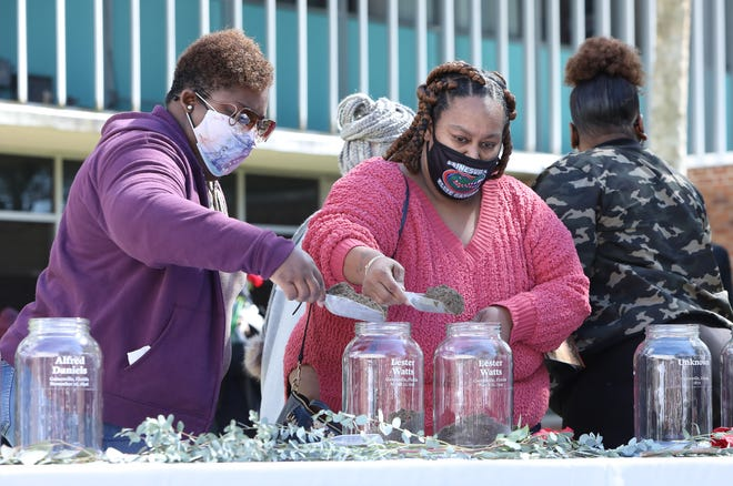 Relatives of Lester Watts, who was murdered in a racial killing in 1942 in Gainesville, pour scoops of soil into glass jars honoring lynching victims in Gainesville during the Gainesville subcommittee of the Alachua County Community Remembrance Project Soil Collection Ceremony held outside the Alachua County Administration Building in Gainesville on Saturday. As part of the the truth and reconciliation process, the ACCRP, in partnership with the Equal Justice Initiative based in Montgomery, Alabama, has collected soil from known sites of lynchings to be preserved in the EJI museum in Alabama, as well as keep the soil on display here in Alachua County as a reminder of the lynchings that occurred in Alachua County.  [Brad McClenny/The Gainesville Sun]
