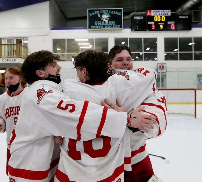 Hingham goalie Theo Jacobs hugs Evan Corbett and Ryan Burns following their 3-0 win over Marshfield in the Patriot Cup Championship game.