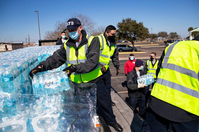 Employees of the City of Corpus Christi unload cases of water to be distributed to residents at the Corpus Christi Natatorium on Friday, Feb. 19, 2021.