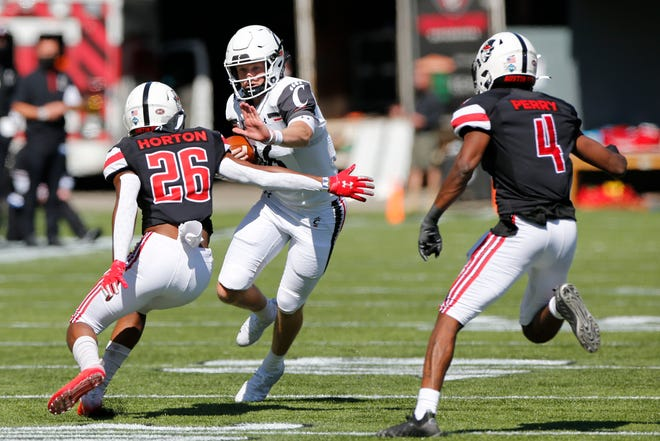 Cincinnati quarterback Michael Lindauer, center, cuts up field between Austin Peay defenders Caleb Horton, left, and Koby Perry during the second half of an NCAA college football game Saturday, Sept. 19, 2020, in Cincinnati, Ohio. Cincinnati beat Austin Peay 55-20. (AP Photo/Jay LaPrete)