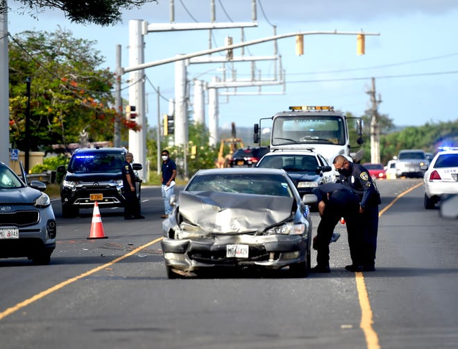 Guam Police Department officers investigate the scene of an auto crash on Route 16 near Our Lady of Peace Memorial Gardens in Barrigada, Feb. 20, 2021.