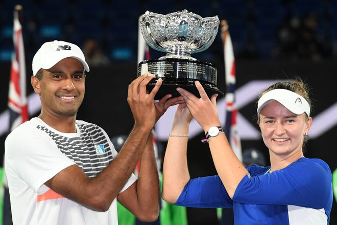 Czech Republic's Barbora Krejcikova (R) and partner Rajeev Ram of the US pose with the championship trophy after winning their mixed doubles final match against Australia's Samantha Stosur and Matthew Ebden on day thirteen of the Australian Open tennis tournament in Melbourne on February 20, 2021.