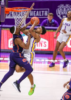 Feb 20, 2021; Baton Rouge, Louisiana, USA;  LSU Tigers guard Cameron Thomas (24) is fouled while driving to the basket against Auburn Tigers guard Devan Cambridge (35) during the first half at the Pete Maravich Assembly Center. Mandatory Credit: Stephen Lew-USA TODAY Sports