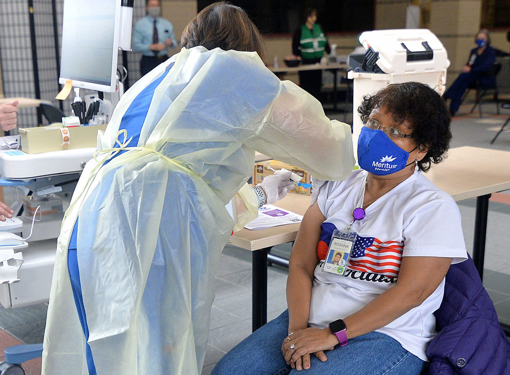 In December 2020, Rosana Bresette, environmental services team at Meritus Medical Center in Hagerstown, Maryland, is the third to receive the COVID-19 vaccine at Robinwood Professional Center. Annie Correces, a school health nurse redeployed to help with the vaccine clinics, administers the vaccine.