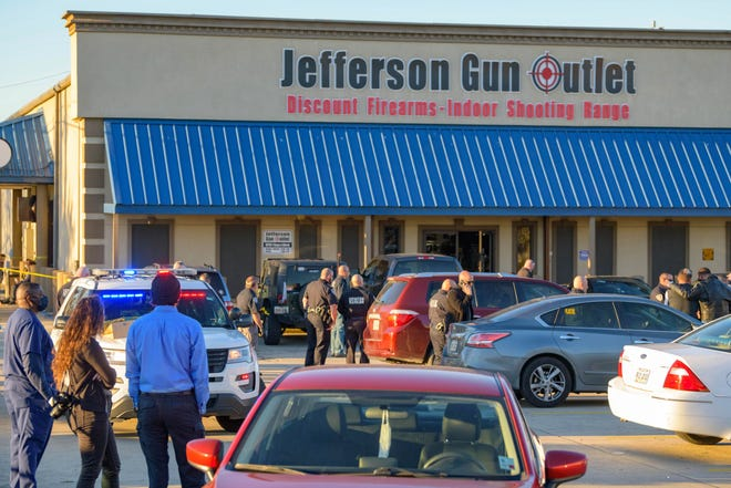Bystanders react at the scene of a multiple fatality shooting at the Jefferson Gun Outlet in Metairie, La., on Feb. 20. A suspect fatally shot two people at a gun store in a suburb of New Orleans and died during gunfire as others engaged the suspect both inside and outside the outlet, authorities said.