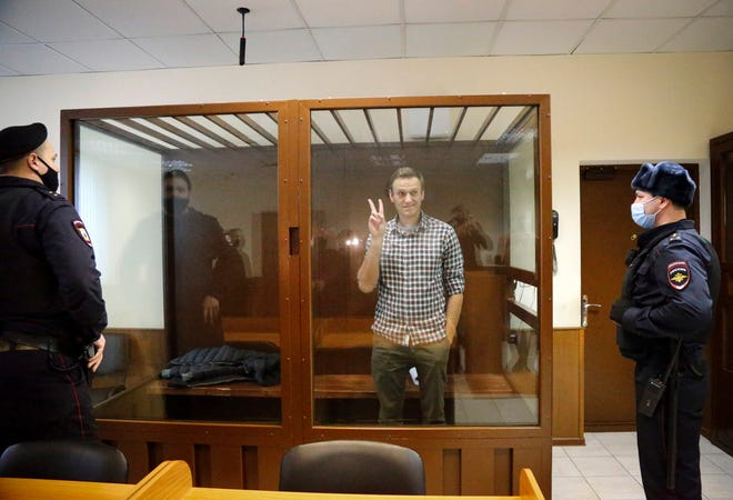 Opposition leader Alexei Navalny stands in a cage in the Babuskinsky District Court in Moscow, Russia, Saturday, Feb. 20, 2021. Two trials against Navalny are being held Moscow City Court one considering an appeal against his imprisonment in the embezzlement case and another announcing a verdict in the defamation case.