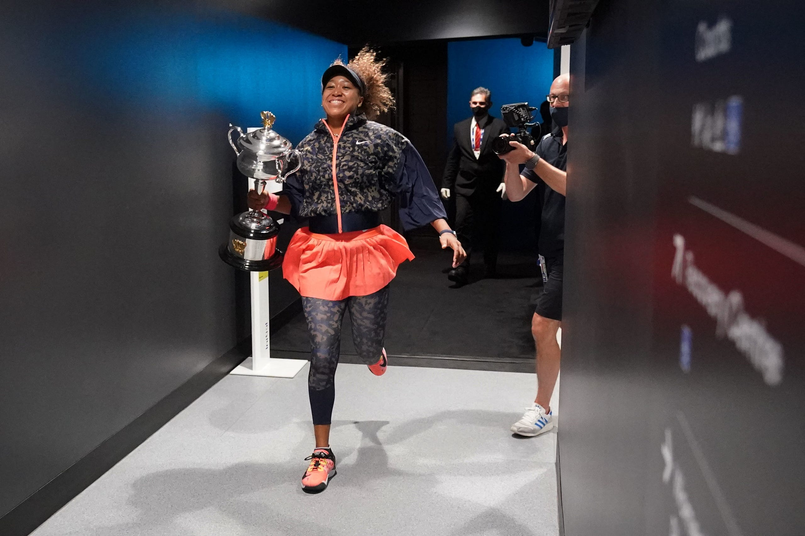 This hand out photo released by the Tennis Australia on February 20, 2021 shows Japan's Naomi Osaka celebrates with the Daphne Akhurst Memorial Cup trophy after her women's singles final match against Jennifer Brady of the US on day thirteen of the Australian Open tennis tournament in Melbourne.