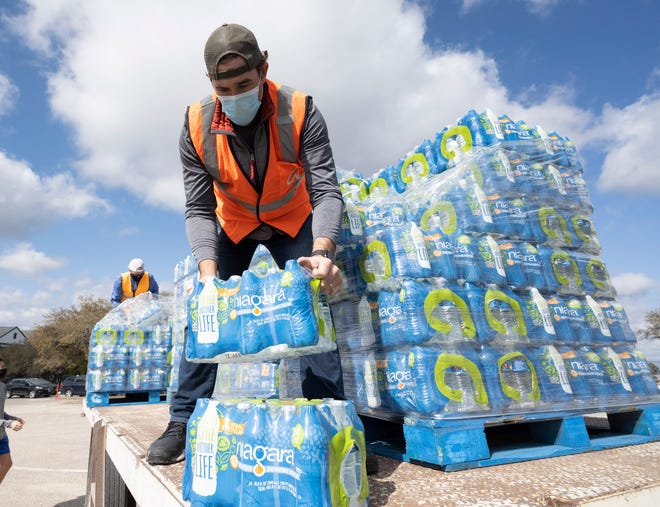 Oak Hill, TX USA Feb. 21, 2021: Volunteers pass out cases of bottled water to desperate western Travis County, TX residents out of tap water for several days due to last week's devastating Texas snowstorm. Drivers were only allowed one case per car after some waiting three hours.