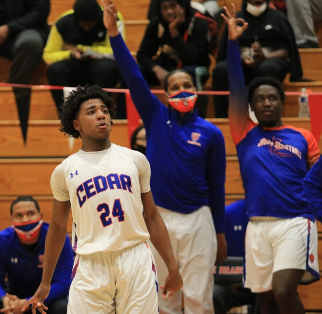 Kashik Brown watches as a three-pointer goes in while bench celebrates in background on Saturday night.