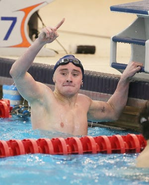 Hudson's Seth Baylor celebrates his first-place finish in the 500-yard freestyle with a time of 4:37.53 at the boys Northeast District Division I Championship at the Spire Institute on Saturday. [Mike Cardew/Beacon Journal]