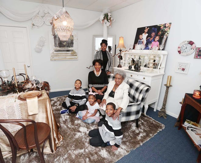 Renea Woods Baylor, center left, sits inside one of her tea rooms inside her downtown business the Tea Lady surrounded by her grandchildren, Tyler Kirkey, 10, back left, TiaMarie Washington, 6, and Trevor Washington, 7, her mother Gertrude Overstreet-Robinson and her daughter, Natasha Overstreet, on Saturday in Akron. Baylor is the third of five generations of entrepreneurs in Northeast Ohio.