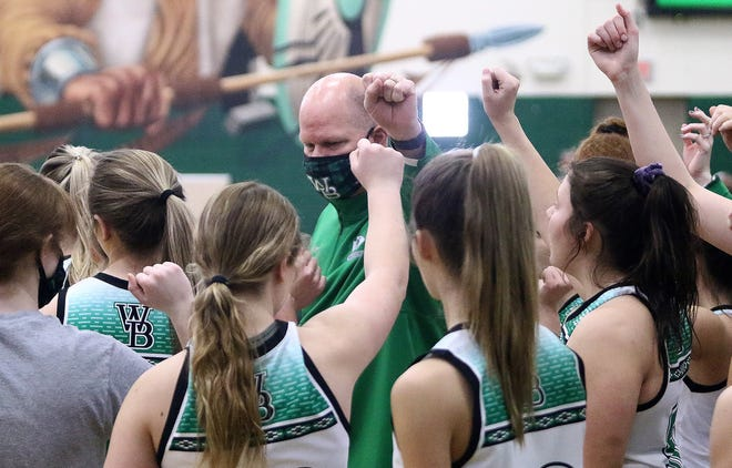 West Branch girls basketball coach Walt DeShields, back, and his team prepare to take the court against Alliance during tournament action at West Branch High School Saturday, February 20, 2021.