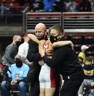 Roland-Story head coach Leland Schwartz (left) and assistant Clint Rothfus embrace Roland-Story's Kade Blume after Blume defeated Williamsburg's Gavin Jensen by sudden victory, 6-4, in the Class 2A 106-pound title match at the state wrestling tournament Saturday in Des Moines. Blume is Roland-Story's first state champion since 1996.