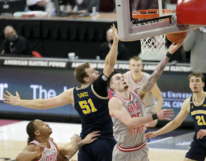 Ohio State forward Kyle Young is guarded by Michigan forward Austin Davis during Sunday's game at Value City Arena.