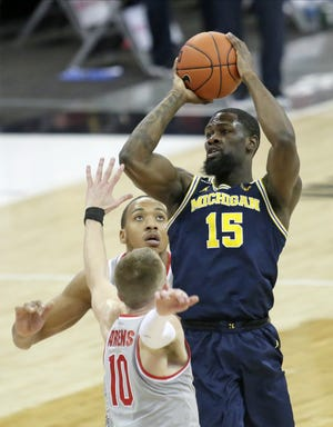 Michigan guard Chaundee Brown is guarded by Ohio State forwards Justin Ahrens and Zed Key on Sunday at Value City Arena.