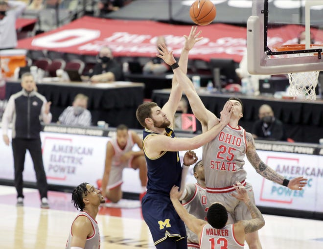 Michigan Wolverines center Hunter Dickinson (1) collides with Ohio State Buckeyes forward Kyle Young (25) under the basket during Sunday's NCAA Division I Big Ten conference basketball game at Value City Arena in Columbus, Ohio, on February 21, 2021.