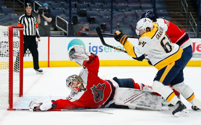 Elvis Merzlikins (90) makes a diving save against Nashville Predators center Mikael Granlund (64) in the second period of the Blue Jackets' 4-2 loss Saturday night at Nationwide Arena. Merzlikins left the game in the third period with an injury.