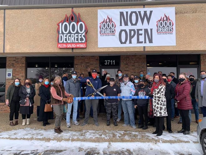 Ribbon cutting – 1000 Degrees Pizza Salad & Wings, 3711 19th St. Holding scissors: owner Austin Rochow. Holding ribbon: Chamber Ambassadors Lori Lee, left, and Kim Davis. Also pictured: other staff, friends and Chamber Ambassadors.