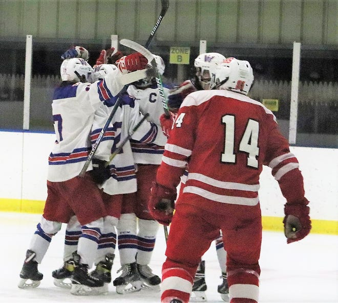 Members of the Winnacunnet High School boys hockey team celebrate after Jake Giacalone's goal in the second period of Saturday's Division II game against Spaulding.