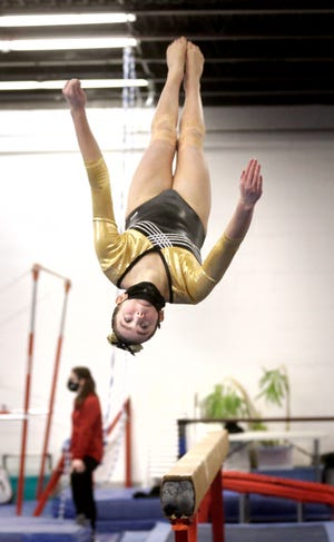 Olivia Priest of North Kingstown flips while dismounting the balance beam Sunday at the Rhode Island Gymnastics Individual State Championship meet in Somerset, Mass..