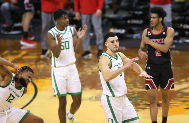 Oregon players including LJ Figueroa, left, Eric Williams Jr. (50) and Chris Duarte celebrate as Utah is called for a double dribble in the closing seconds of the Ducks' 67-64 win on Saturday at Matthew Knight Arena.