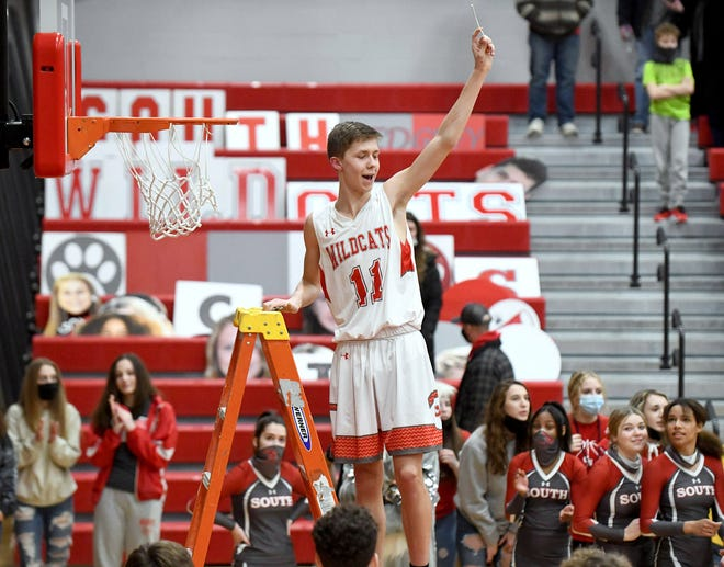 Canton South senior Gavin Burchfield holds up a piece of net he cut after Canton South beat Minerva winning a share of  the Eastern Buckeye Conference Saturday, February 20,2021.