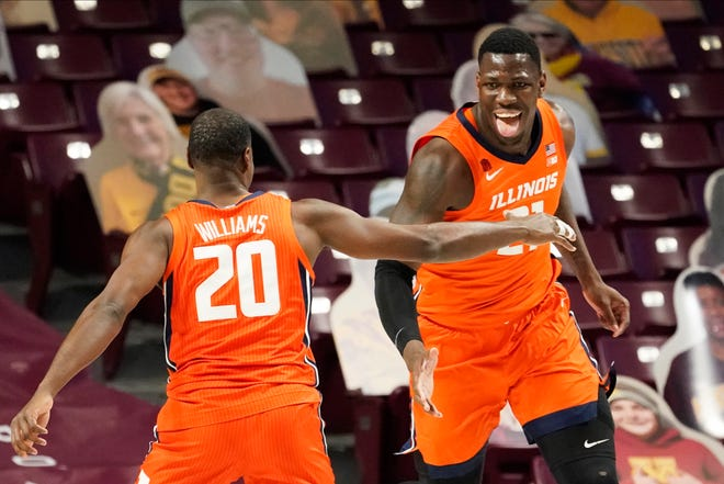 Illinois' Kofi Cockburn, right, celebrates one of his shots with teammate Da'Monte Williams (20) in the first half of an NCAA college basketball game on Saturday, Feb. 20, 2021, in Minneapolis.