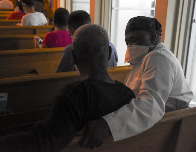 Dr. Yusif Addae checks in on Ken McNeil of Newtown, who received a vaccination 15 minutes earlier during the COVID-19 vaccination clinic at Light of the World International Church on Sunday. People who received their vaccination took a seat in the chapel and waited 15 minutes as a precaution for any side effects. Ken had no issues or side effects.  February 21, 2021;   Herald-Tribune photos/Carla Varisco