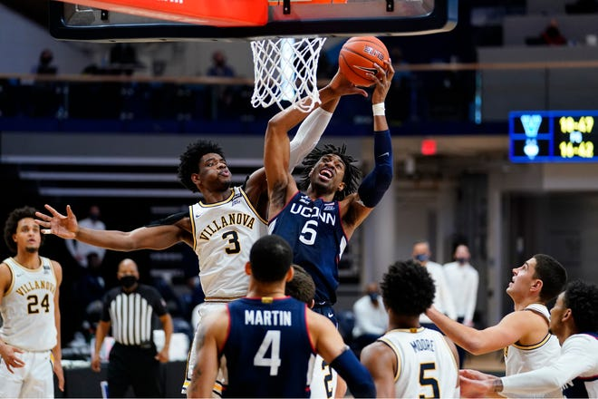 Connecticut's Isaiah Whaley (5) and Villanova's Brandon Slater (3) leap for a rebound during the second half of an NCAA college basketball game, Saturday, Feb. 20, 2021, in Villanova, Pa.
