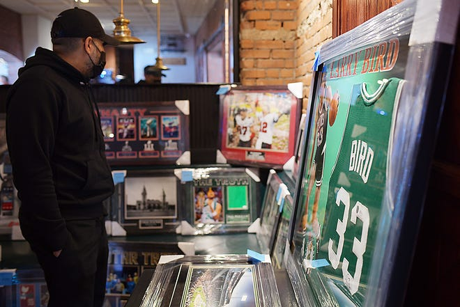 The Boys & Girls Club of Worcester and members of the sheriff's department organized a fundraiser to benefit Woodrow Adams Jr. and his family at the Compass Tavern Sunday. A man peruses framed sports memorabilia for sale that will benefit Woordrow Adams Jr. and his family.