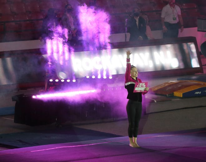 Alabama gymnast Kaylee Quinn is introduced before the Power of Pink meet with LSU. COVID-19 restrictions forced a change in the program where gymnasts normally escorted a breast cancer survivor onto the floor during introductions. Gymnasts introduced Friday, Feb. 19, 2021, carried a sign bearing the name of a cancer survivor. [Staff Photo/Gary Cosby Jr.]
