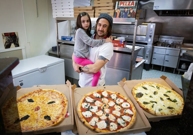 Frankie Abbatecola and his daughter Lily pose with a selection of pizzas inside I Love Frankie's, Worcester's Best Pizza at 90 Providence St.