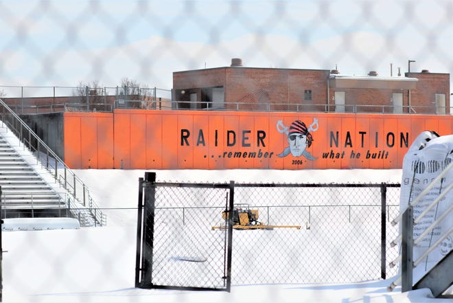 Construction equipment sits at the football stadium at Ryle High School waiting for the snow to melt, Feb. 20, 2021, as the four high schools in the Boone County school district are putting artificial turf in their stadiums.