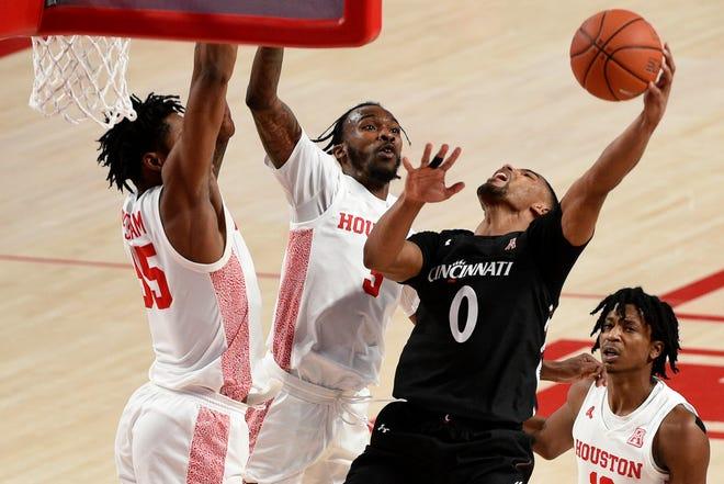 Cincinnati guard David DeJulius (0) shoots as Houston forward Fabian White Jr., left, and guard DeJon Jarreau, center, defend during the first half of an NCAA college basketball game, Sunday, Feb. 21, 2021, in Houston.