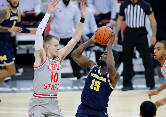 Michigan Wolverines guard Chaundee Brown shoots against Ohio State Buckeyes forward Justin Ahrens during the first half at Value City Arena, Feb. 21, 2021 in Columbus, Ohio.
