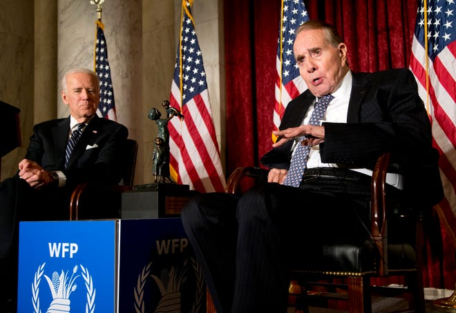 FILE - In this Dec. 11, 2013, file photo former Senate Majority Leader Bob Dole, right, speaks after being presented with the McGovern-Dole Leadership Award by Vice President Joe Biden, left, to honor his leadership in the fight against hunger, during the 12th Annual George McGovern Leadership Award Ceremony hosted by World Food Program USA, on Capitol Hill in Washington.