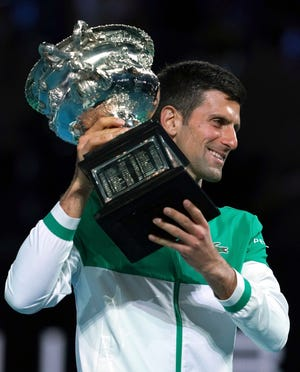 Serbia's Novak Djokovic poses with the Norman Brookes Challenge Cup after defeating Russia's Daniil Medvedev in the men's singles final on Sunday at the Australian Open in Melbourne, Australia.