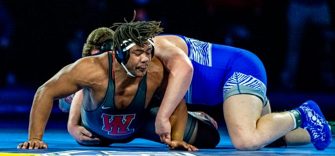 Mariere Omonode of West Lafayette High School tries to get away from control by Reeve Muncie of Carroll (Ft. Wayne) High School on Saturday, Feb. 20, 2021, during IHSAA wrestling finals at Bankers Life Fieldhouse in Indianapolis. Muncie won the 285 pound final.