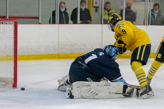 Seth Ferguson wraps the puck around Livonia Stevenson goalie Brenden Stroble for Hartland's final goal in a 5-1 victory on Saturday, Feb. 20, 2021 at Hartland Sports Center.