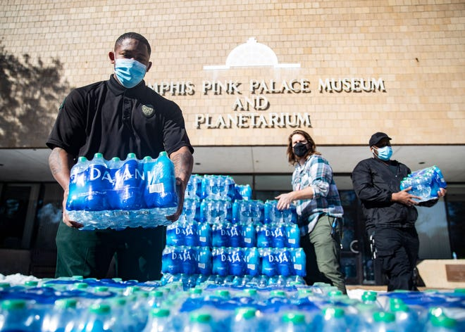 Volunteers distribute cases of drinking water to residents as Shelby County remains under a boil water notice at the Pink Palace MuseumÊ in Memphis, Tenn., on Friday, Feb. 21, 2021.